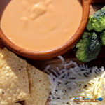 beer horseradish cheese sauce in bowl with broccoli and chips