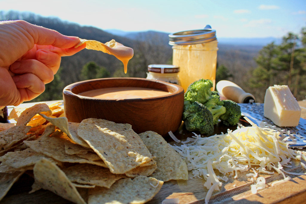 dipping chip into cheese sauce with mountain view
