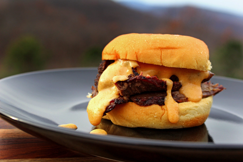 chuck roast sandwich with cheese sauce oozing out of it