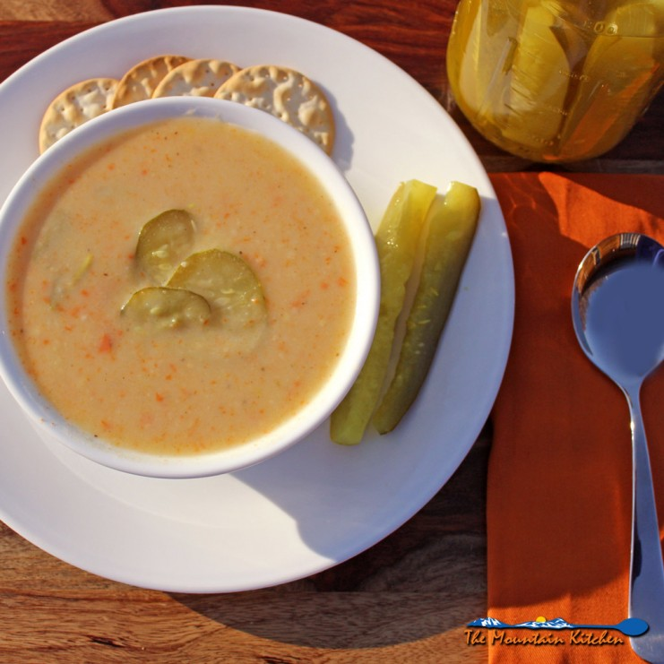 dill pickle soup in bowl on a plate with pickles and crackers