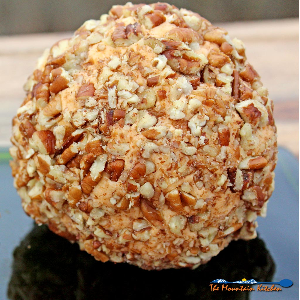 Mama's Christmas Cheese Ball is made with Velveeta, cream cheese, and extra-sharp cheddar cheese, and coated in chopped pecans. Its simplicity is delicious.