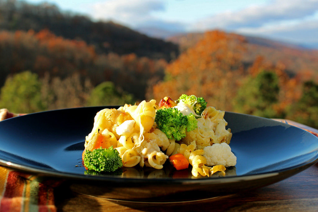 easy roasted vegetable pasta on a plate with mountain view