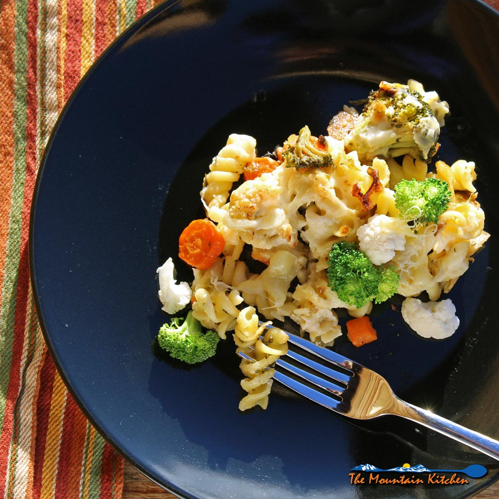 This easy roasted vegetable pasta bake combines sweet herb roasted vegetables and pasta with a creamy cheese sauce. A delicious vegetarian meal!