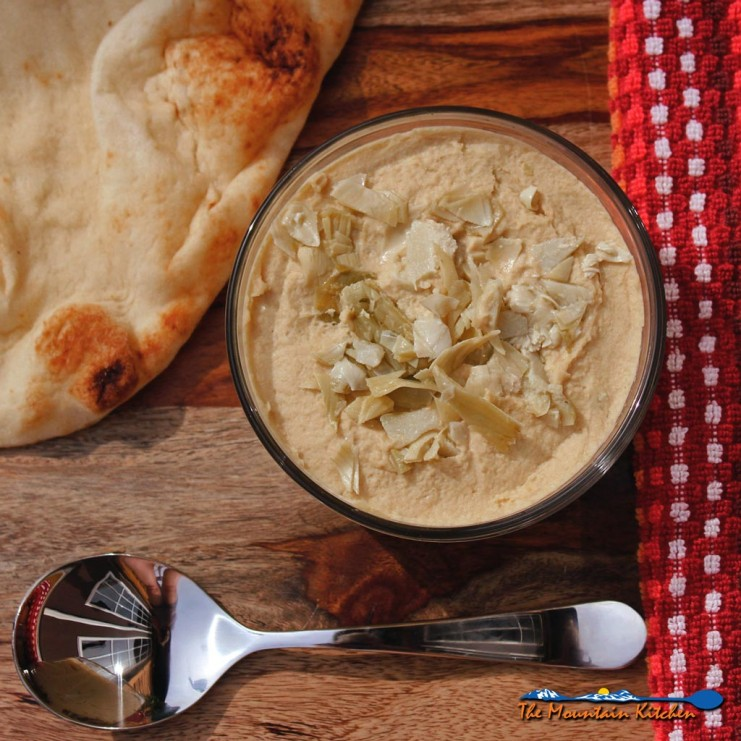 Marinated Artichoke Hummus in bowl ready to eat with pita bread and spoon