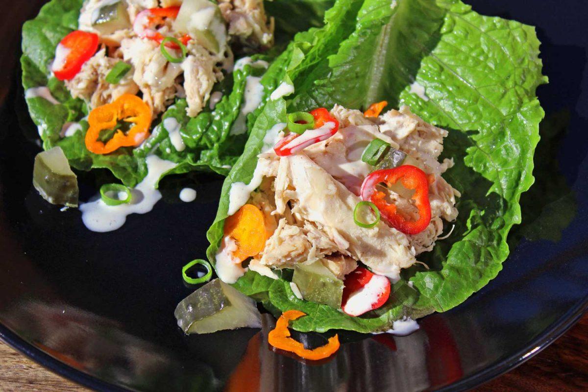saucy crock-pot chicken lettuce wraps on black plate