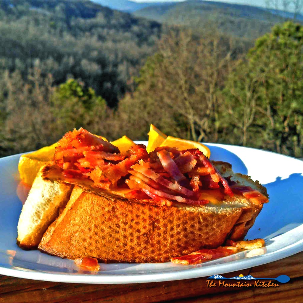 French bread egg in a basket is made with an egg cooked over easy inside a hole in the center, topped with melted cheese and sprinkled with bacon bits. Yum! #frenchbread #egg #egginabasket #egginahole #recipe #breakfast #brunch