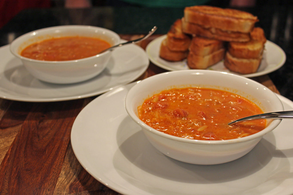 This vegetarian version of tomato orzo soup is made of tender pasta in a creamy tomato broth served with buttery, grilled cheeses made of Gruyère cheese. | TheMountainKitchen.com
