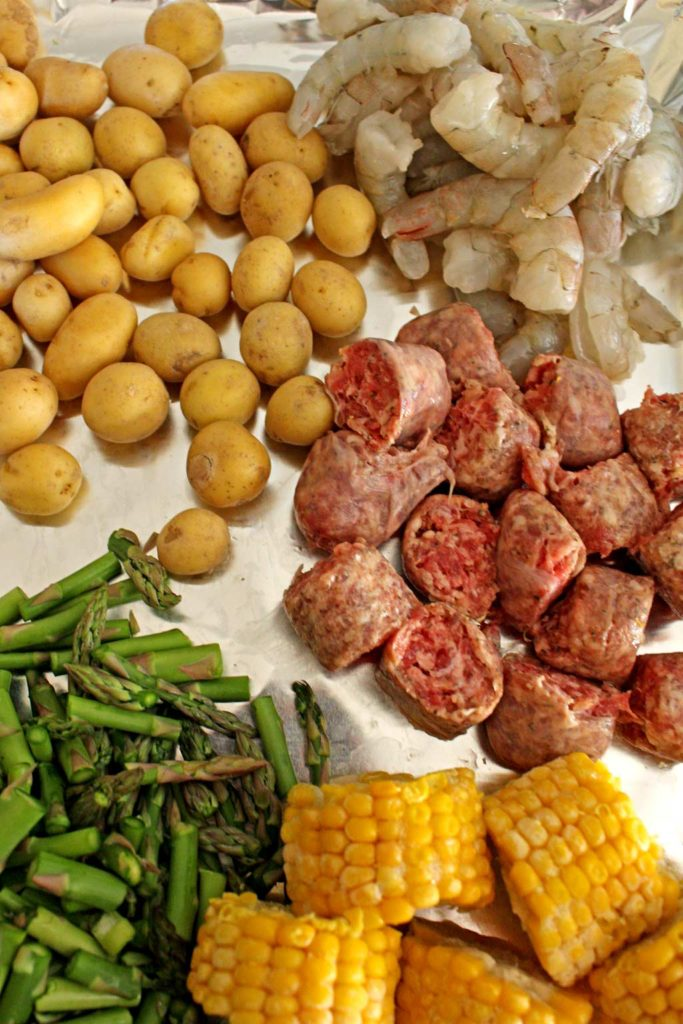 Cajun spiced shrimp, juicy andouille sausage, asparagus, potatoes and corn make up a flavorful meal in minutes. Make this Sheet Pan Cajun Dinner tonight!   TheMountainKitchen.com