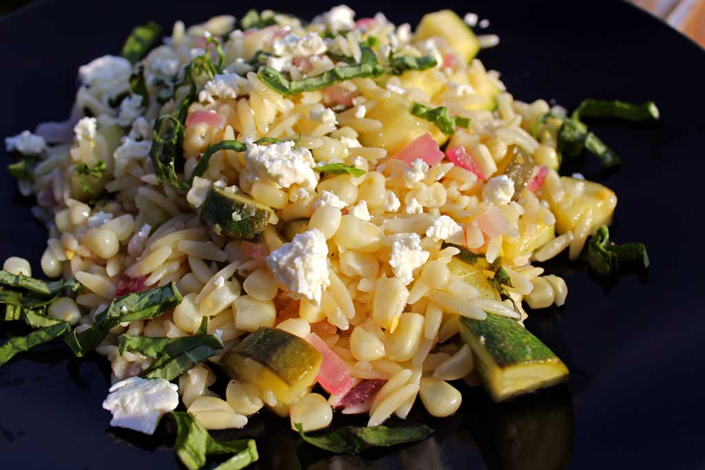 Summer is bursting with flavor in this corn zucchini orzo salad. Seasonal vegetables combined with lemony orzo and feta cheese for a quick pasta salad. Yum!   TheMountainKitchen.com