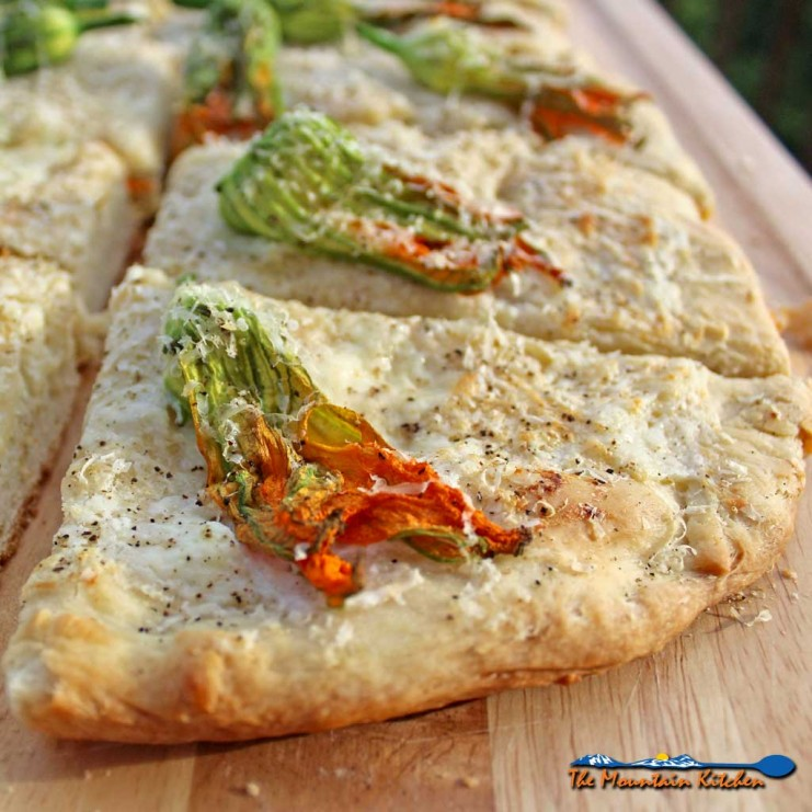 Squash blossom focaccia bread with delicate squash blossoms, creamy ricotta cheese and parmesan cheese baked until golden brown. A great summer side dish! | TheMountainKitchen.com