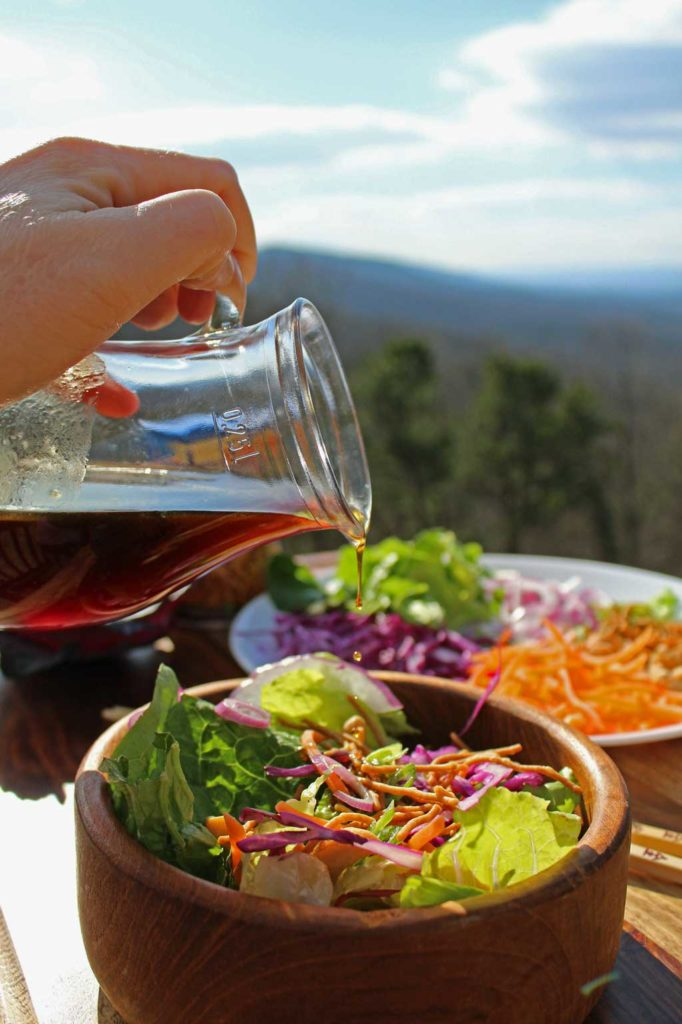 pouring dressing onto asian crunch salad with mountain view