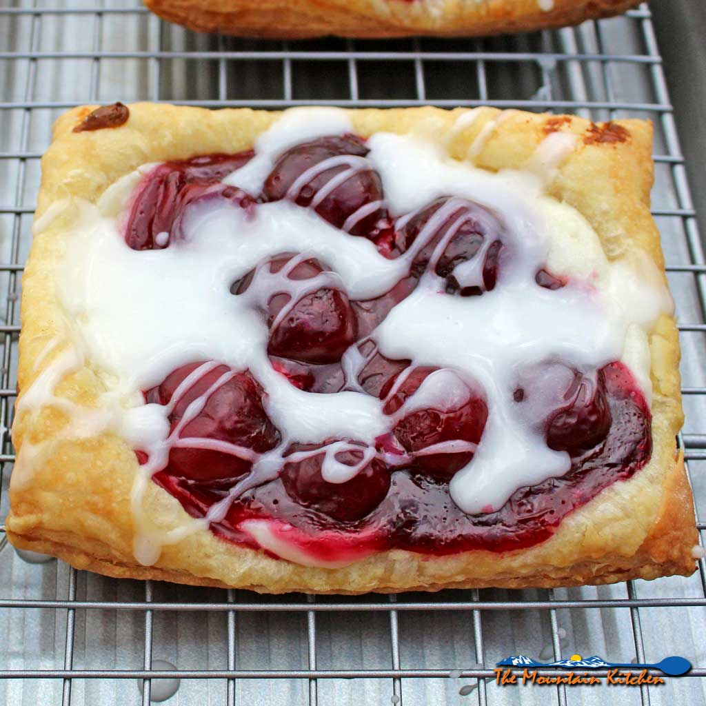 Yum! Enjoy this light, flaky, and easy cherry cream cheese danish with vanilla glaze in the comfort of your home, for breakfast any day of the week. | TheMountainKitchen.com