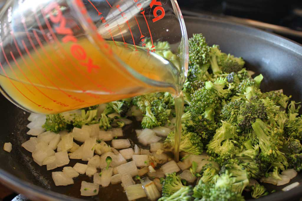pouring vegetable broth into broccoli and onions
