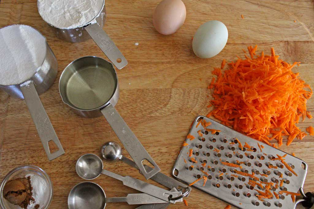 kitchen equipment, shredded carrots and eggs on cutting board