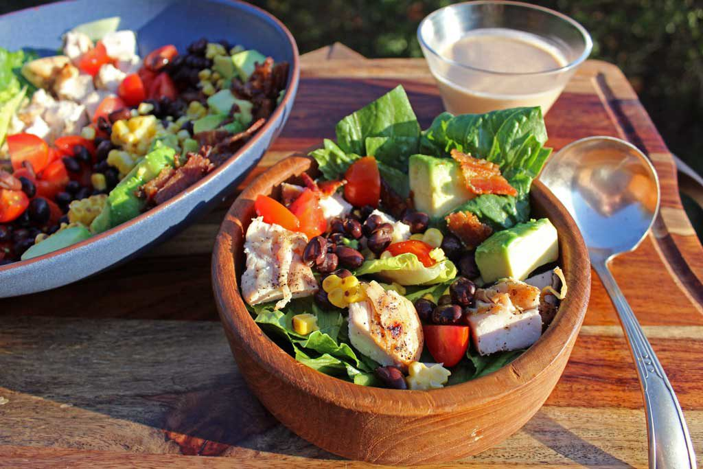 This Grilled Chicken Southwest Salad is packed with black beans, tomatoes, grilled corn, bacon, avocado and romaine lettuce, topped with BBQ Ranch Dressing.
