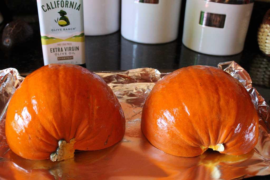 split pumpkin on baking sheet