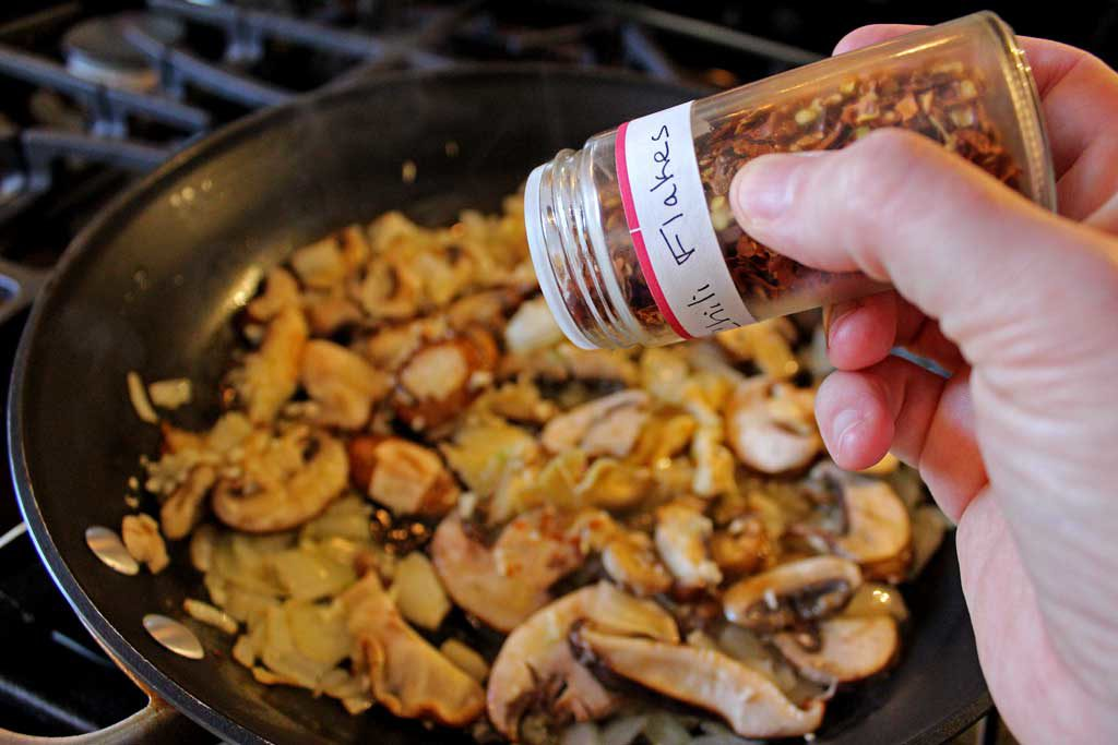 adding red pepper flakes to the pan of mushrooms