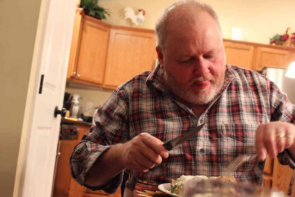 David licking his lips at supper table