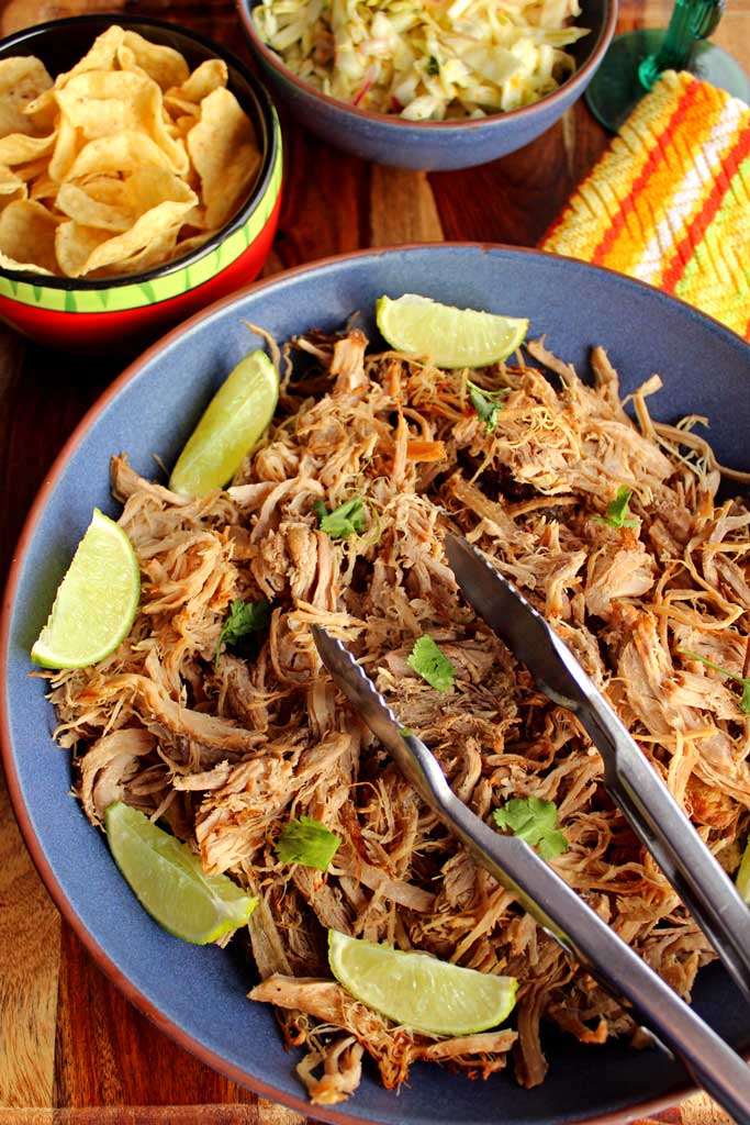 Oven-Roasted carnitas a Mexican dish of braised pork in a broth, then shredded and cooked until crispy. Serve in tacos, burritos or nachos!