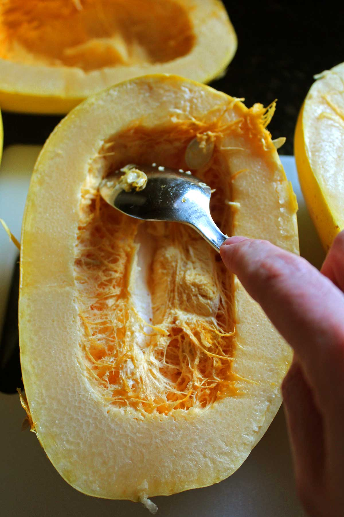 spooning the pulp out of the squash