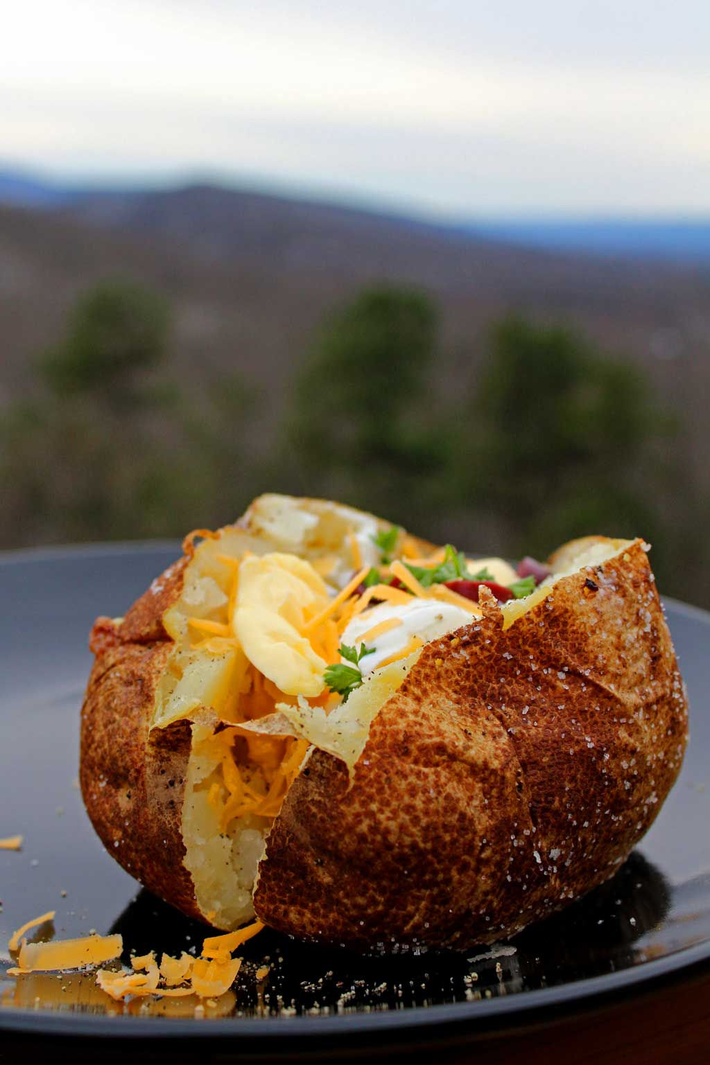 Steakhouse baked potatoes have a salted crispy, golden skin with a light with a warm fluffy center. Learn how to make these perfect baked potatoes at home!