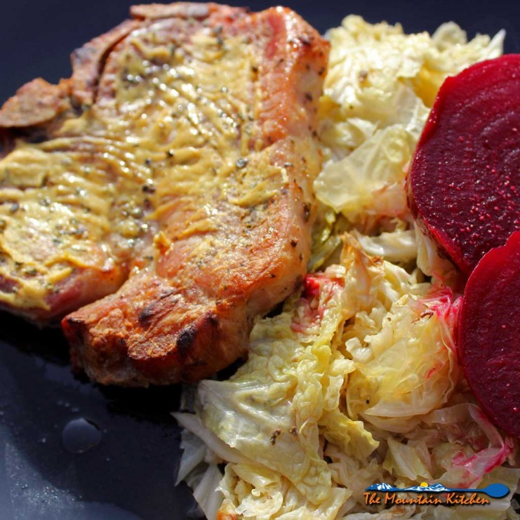 Dijon pork chops dredged in lemony Dijon mustard with herbs, roasted on a bed of cabbage in a rich broth. Try with roasted beets with apple cider vinegar! | TheMountainKitchen.com