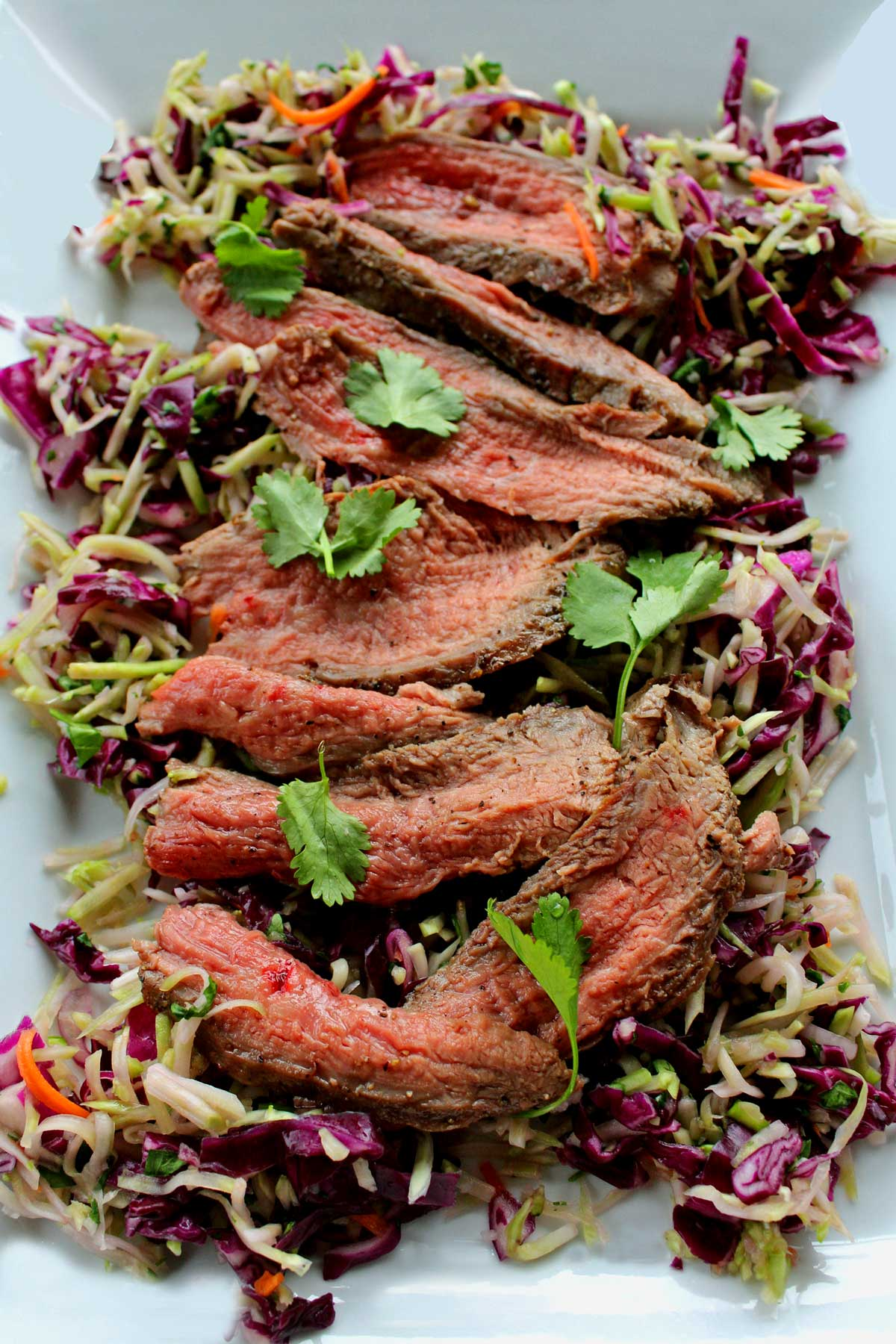 This is a quick and easy Grilled Thai Steak Salad is infused with such amazing Asian flavor. Crisp salad paired with grilled flank steak. Try it tonight!