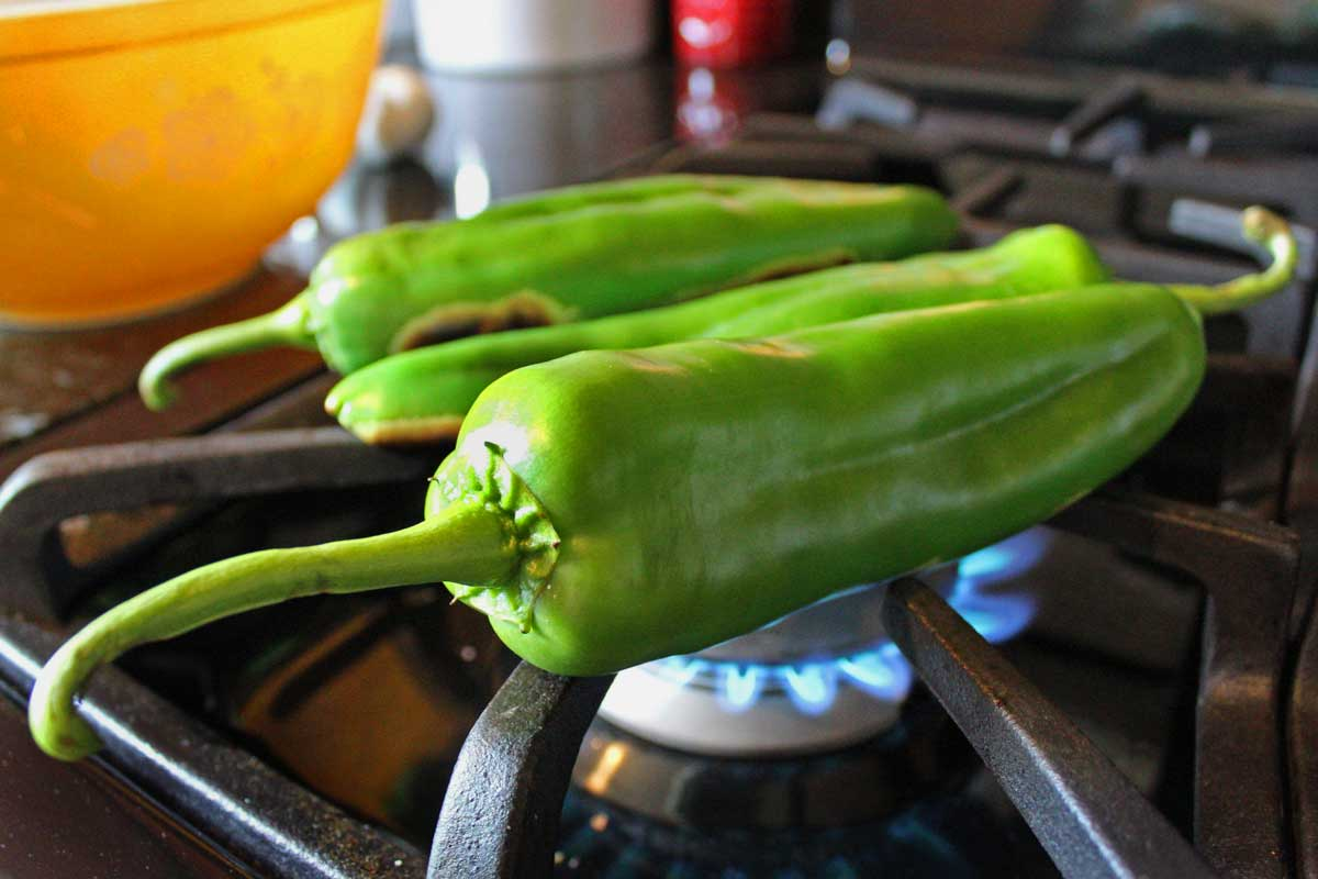 hatch chili roasting over gas stove flame