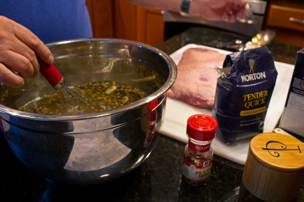 whisking brine together with brisket and ingredients