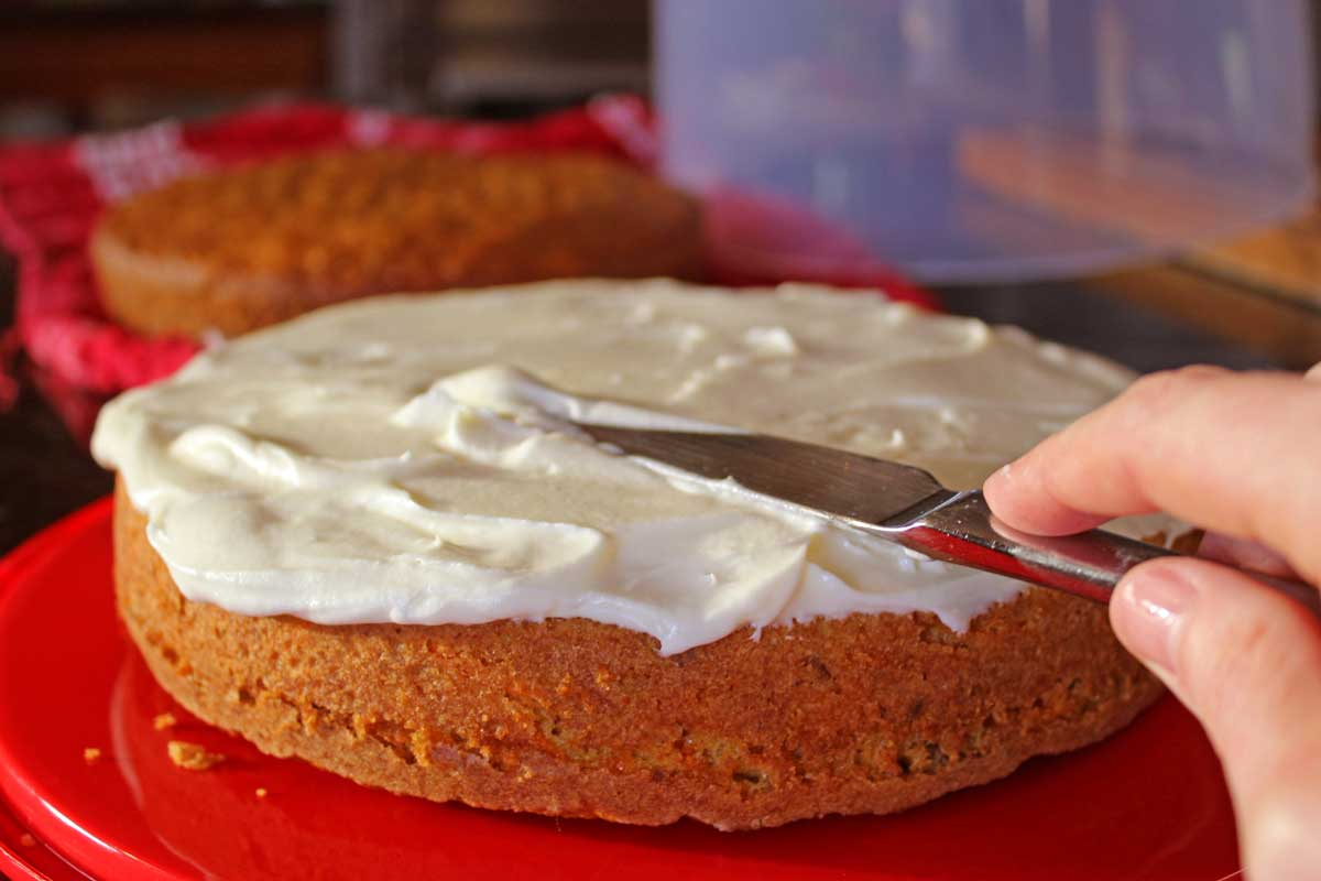 spreading icing on ultimate carrot cake