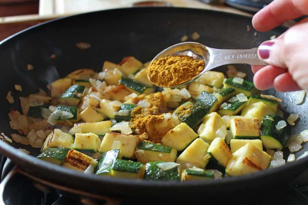 Curry in a measuring spoon being added to the pan of zucchini and onions.