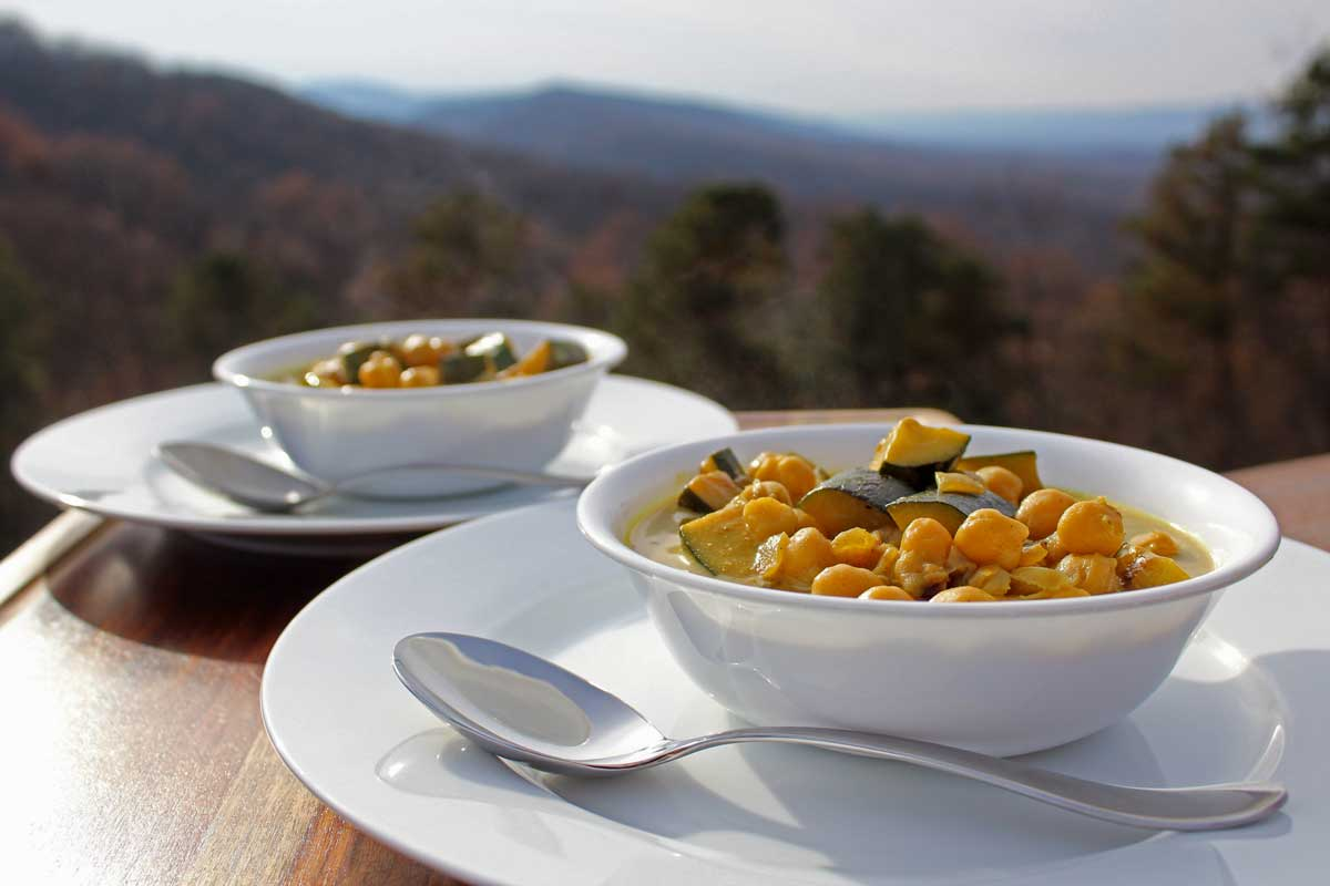 Two bowls of stew with a view of the mountains in the background.