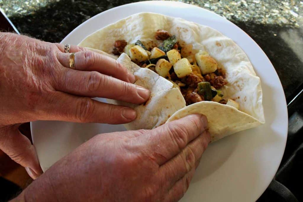 rolling up the breakfast burrito