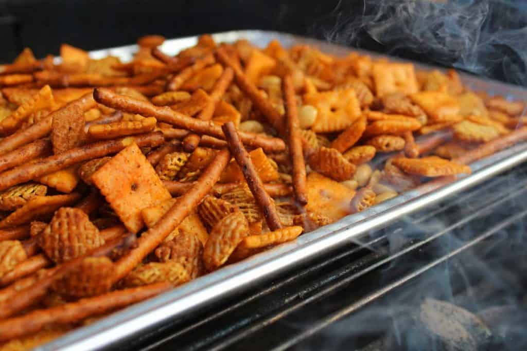 smoke kissing the snack mix on the grill