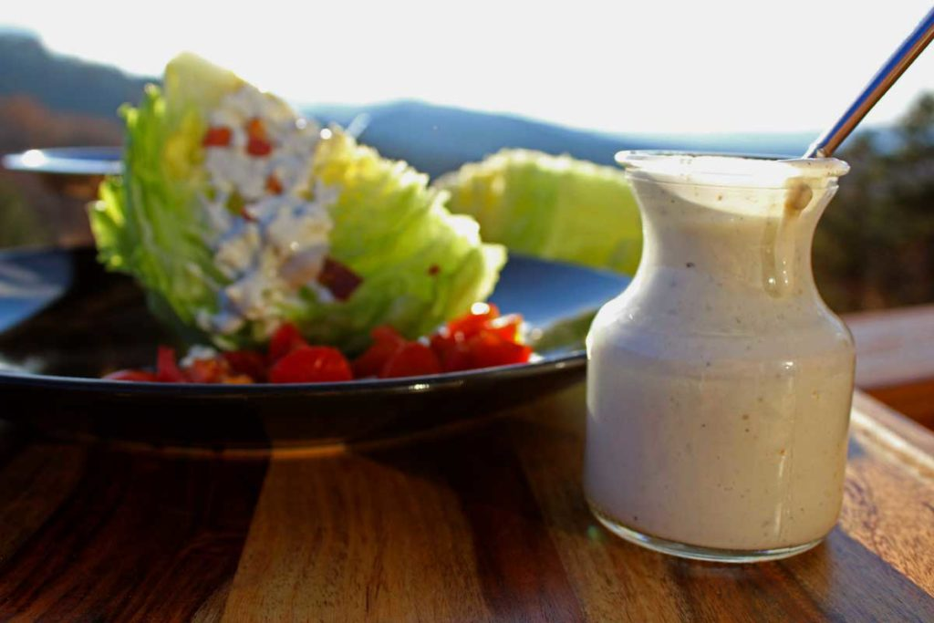 jar of blue cheese dressing with a classic wedge salad and mountains in the background