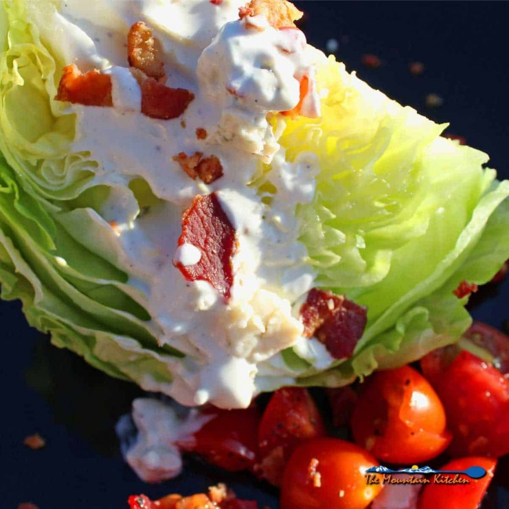 This delicious classic wedge salad has crisp iceberg lettuce wedges topped with creamy homemade blue cheese dressing, smoky bacon, and juicy tomatoes.