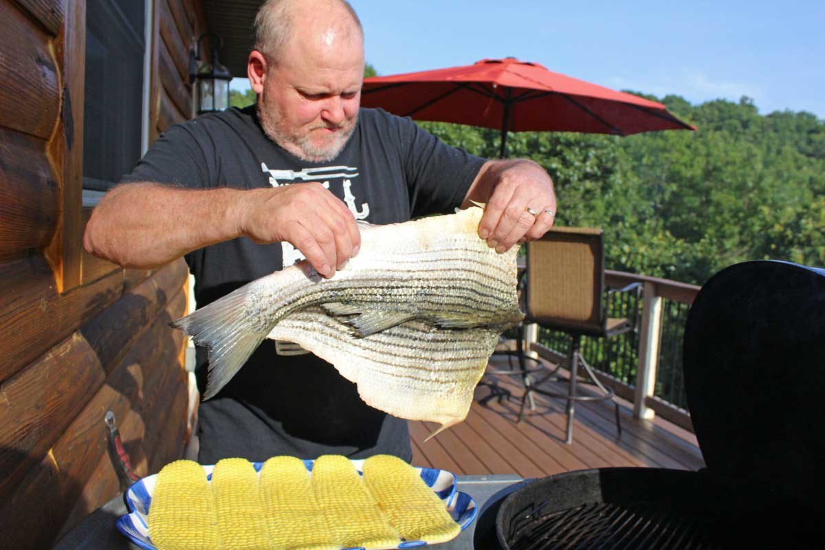David placing the fish on the grill