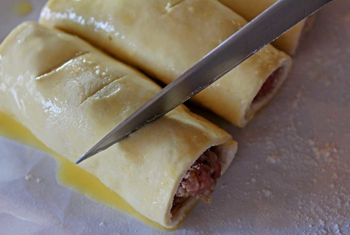 slitting the sausage rolls with a knife