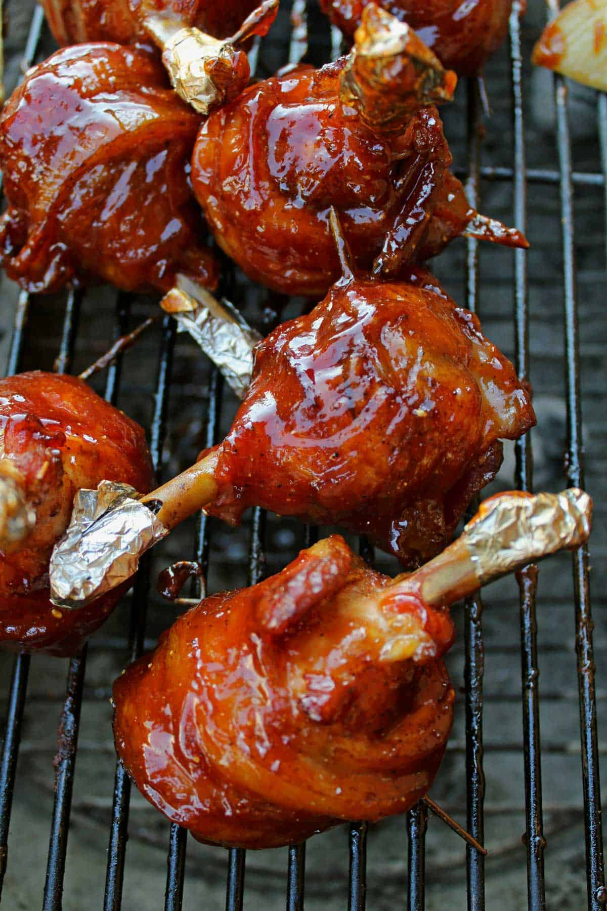 BBQ chicken lollipops are chicken drumsticks seasoned with a dry rub, wrapped in bacon and smoked with barbecue sauce. An inexpensive way to please a crowd!