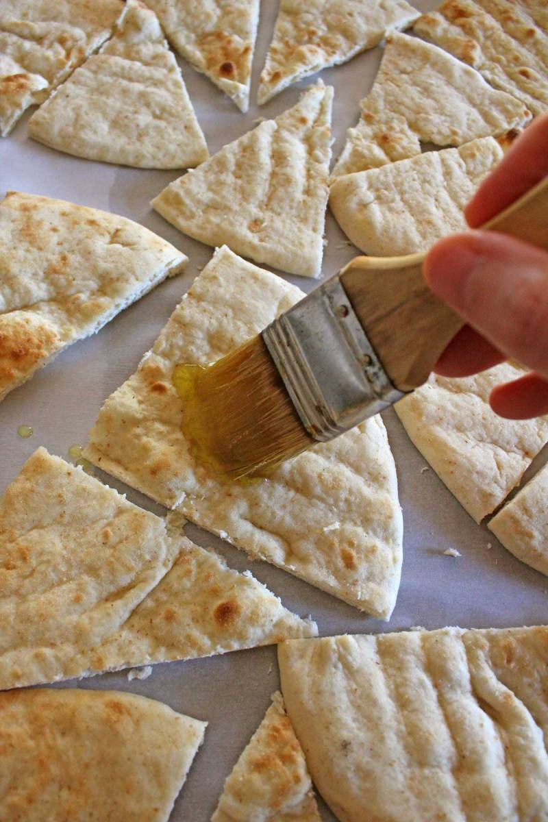brushing pita bread with oil