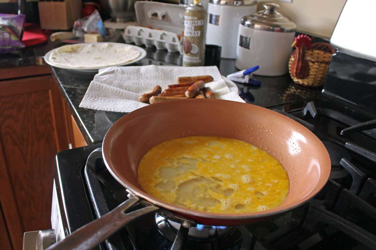 a skillet with eggs cooking on stove