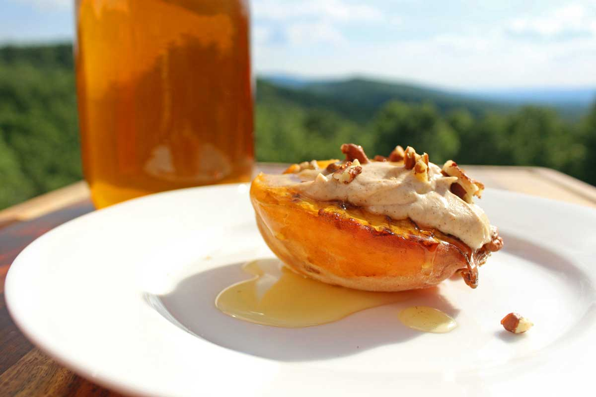 grilled peach topped with cinnamon ricotta creme pecans and honey