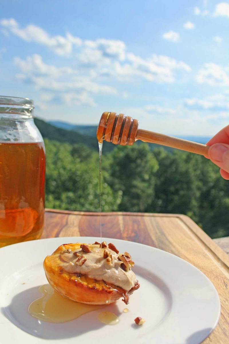 drizzling honey onto peach with mountain view
