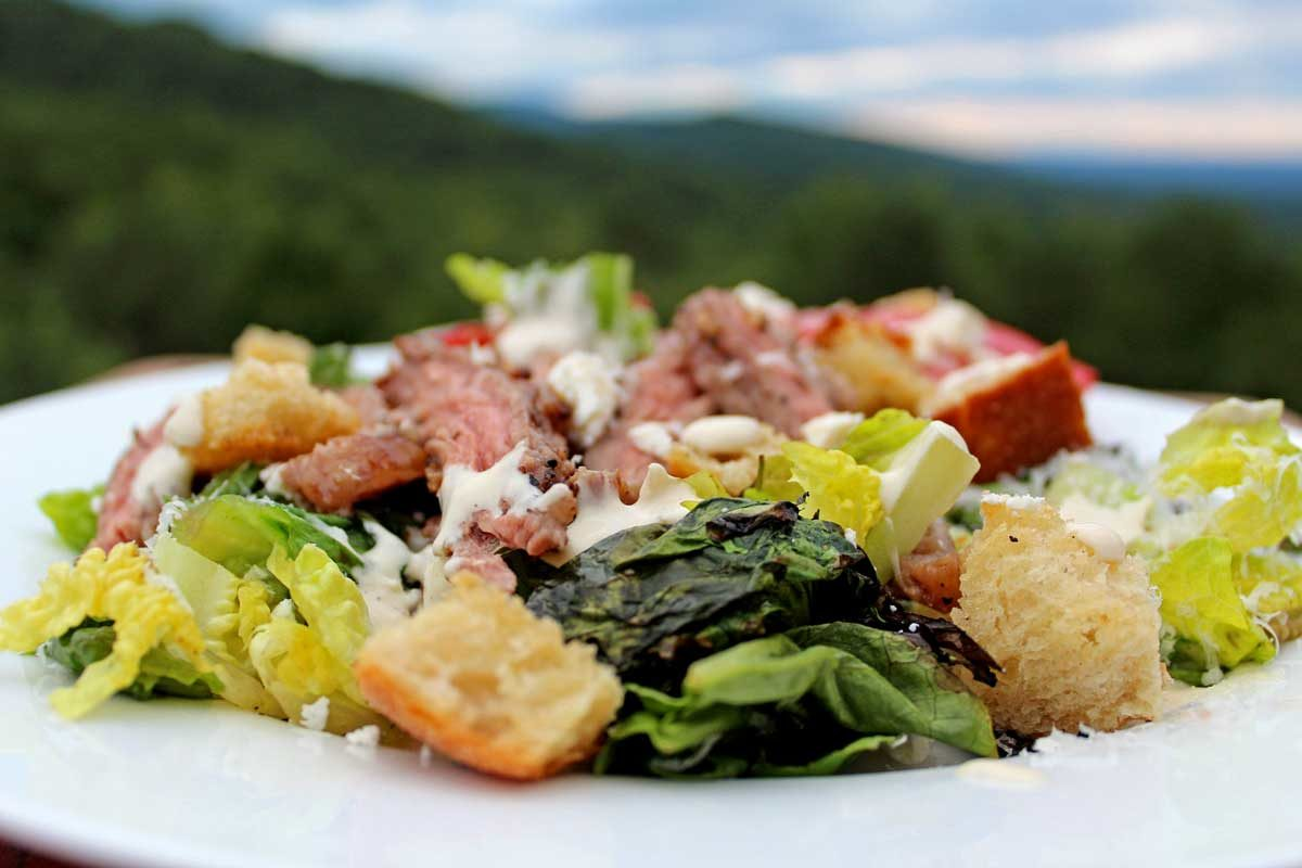plate of grilled steak Caesar salad with mountain view