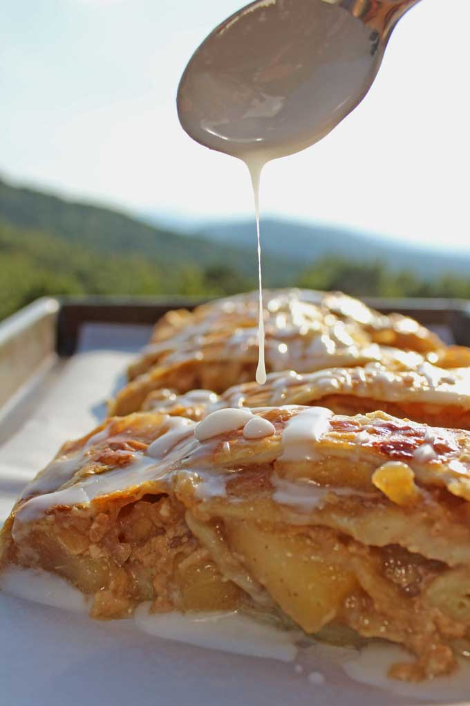Caramel apple strudel, made of rich buttery layers of flaky puff pastry wrapped around warm spiced apples and salty caramel, drizzled with vanilla glaze.