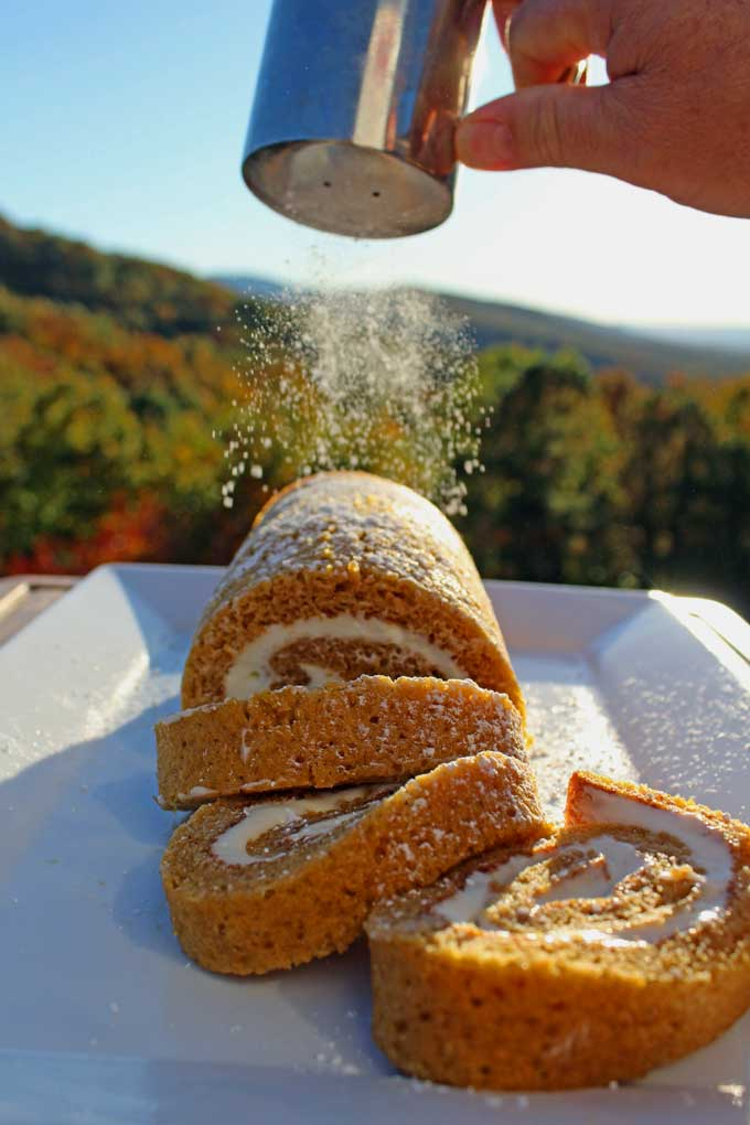 dusting the easy pumpkin roll with powdered sugar with mountain view