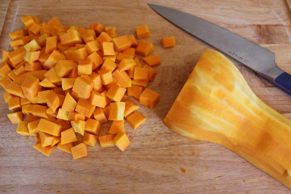 cut butternut squash on cutting board with knife