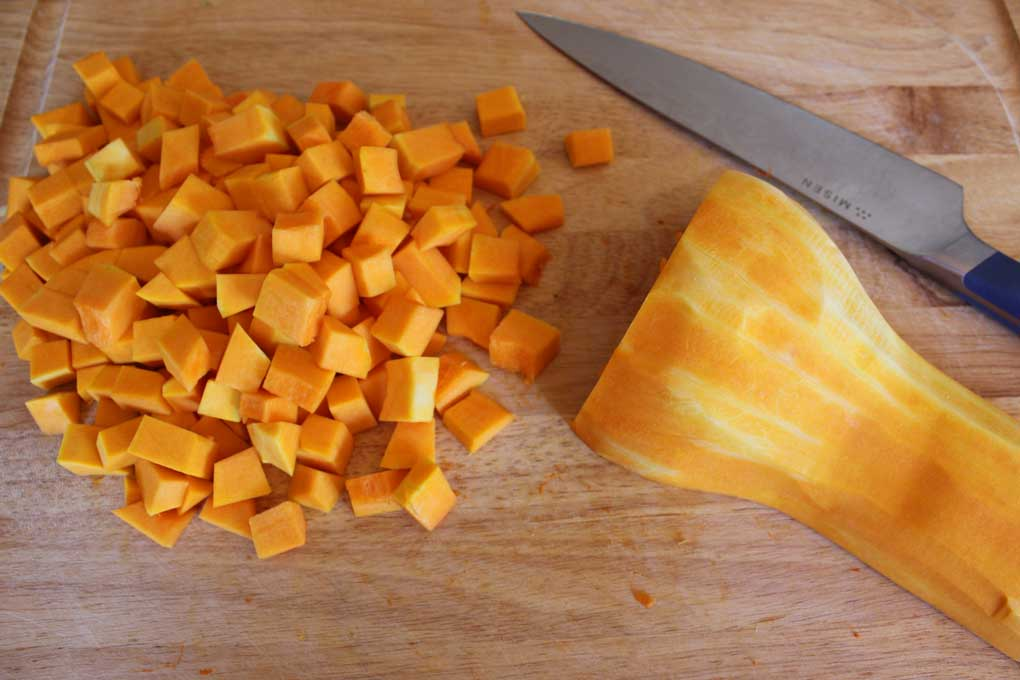 cut butternut squash on cutting board with knife