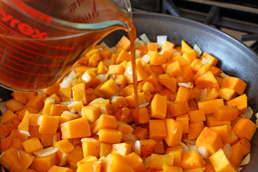 adding vegetable broth to squash mixture in skillet
