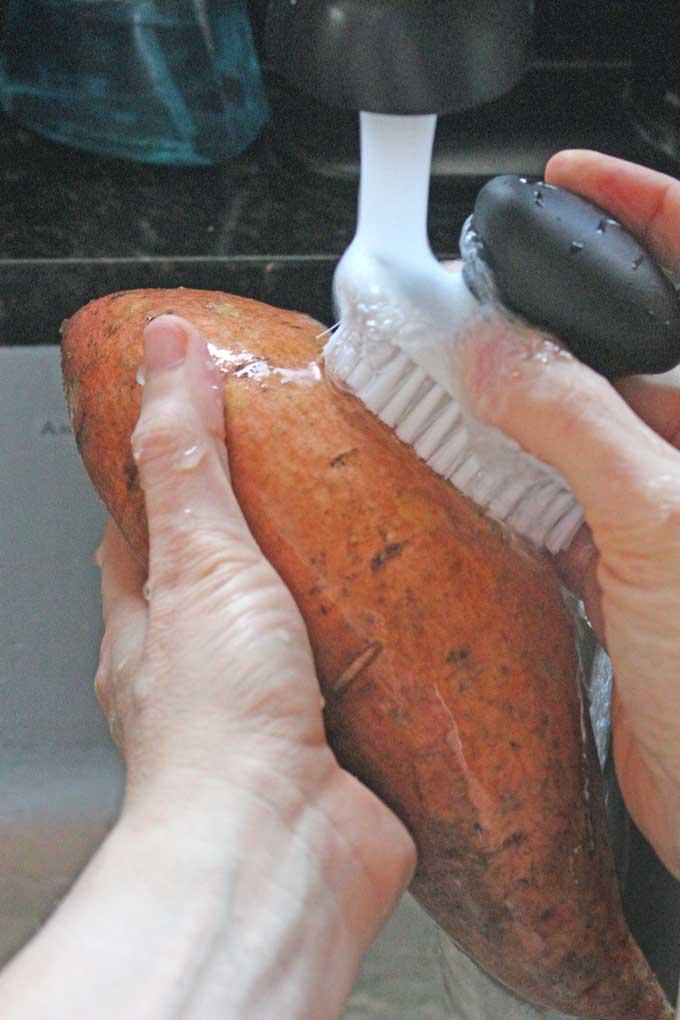 washing potato with vegetable brush